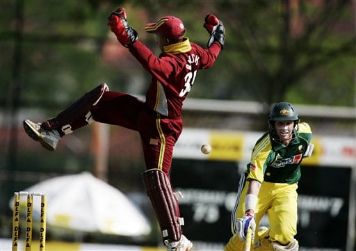 Australian batsman Micahel Hussey, right, runs to his crease as the West Indies' wicketkeeper Carlton Baugh struggles to handle a high through in their tri-series match in Kuala Lumpur on Monday.