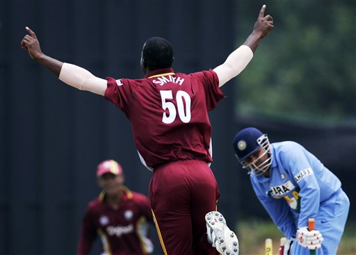 West Indies' bowler Dwayne Smith, left, celebrates after bowling Indian batsman Virender Sehwag for 1 run in their tri-series match in Kuala Lumpur on Wednesday.