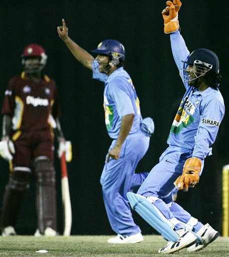India's Mahendra Singh Dhoni, right, and Suresh Raina share celebration styles after the stumping of India's Dwayne Bravo in their tri-series cricket match in Kuala Lumpur on Wednesday.