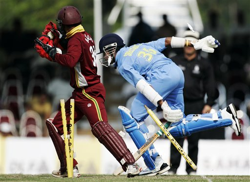 Indian batsman S Sreesanth, right, races into his crease but not before he is run out by the West Indies' wicketkeeper Carlton Baugh for no score in their tri-series match in Kuala Lumpur on Wednesday.