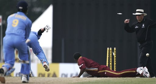 Indian batsman Sachin Tendulkar, second left, is run out for 65 runs after his batting partner Rudra Pratap Singh, left, had a drive deflected onto the stumps by West Inides' bowler Marlon Samuels, right, in their tri-series match in Kuala Lumpur on Wednesday.