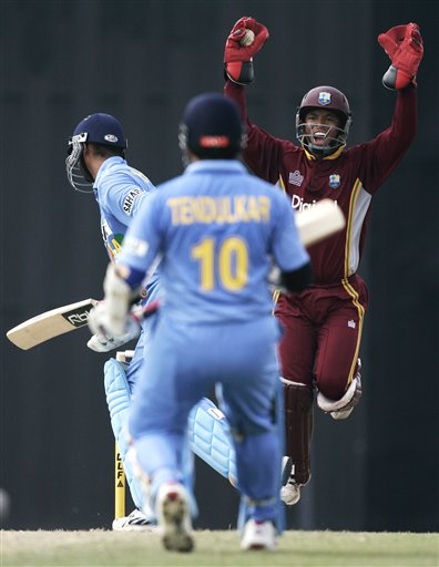 West Indies' wicketkeeper Carlton Baugh, right, celebrates catching out Indian batsman Harbhajan Singh, left, for 37 runs as Sachin Tendulkar looks on in their tri-series match in Kuala Lumpur on Wednesday.