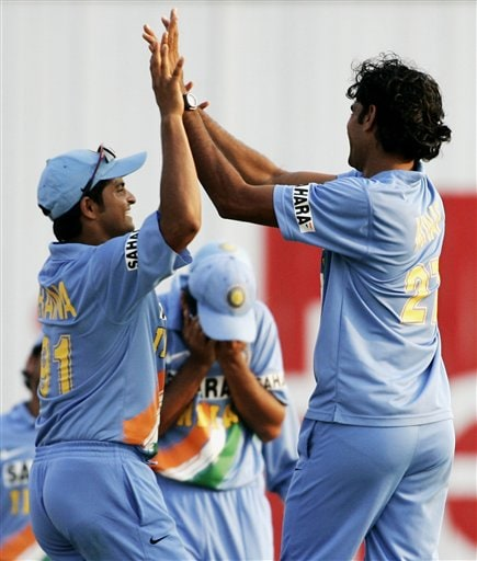India's Manuf Patel, right, and Suresh Raina celebrate the wicket of West Indies' batsman Ramnaresh Sarwan for 2 runs as their captain Rahul Dravid, center, holds his head after he was hit with the ball during the celebrations in their tri-series match in Kuala Lumpur on Wednesday.