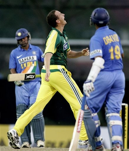 Australia's Stuart Clark, center, celebrates after he caught and bowled India's Mohammad Kaif, left, for 21 as Rahul Dravid looks on in their tri-series cricket match in Kuala Lumpur on Friday.