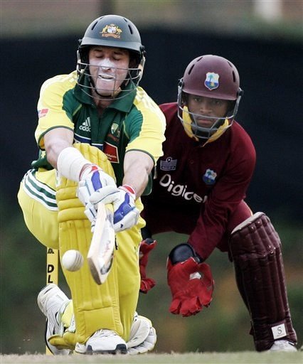 Australian batsman Michael Hussey, left, plays a sweep shot as West Indies' wicketkeeper Carlton Baugh looks on during their final of the tri-nations series in Kuala Lumpur on Sunday.