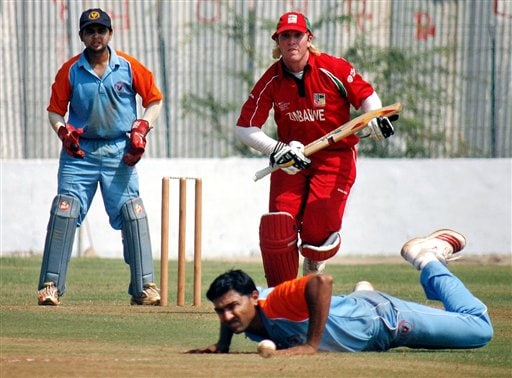 Vishwajit Solanki of Gujarat Cricket Association XI tries to stop a ball as B Taylor of Zimbabwe runs during a practice match between Zimbabwe and GCA XI ahead of ICC Champions Trophy in Ahmedabad.