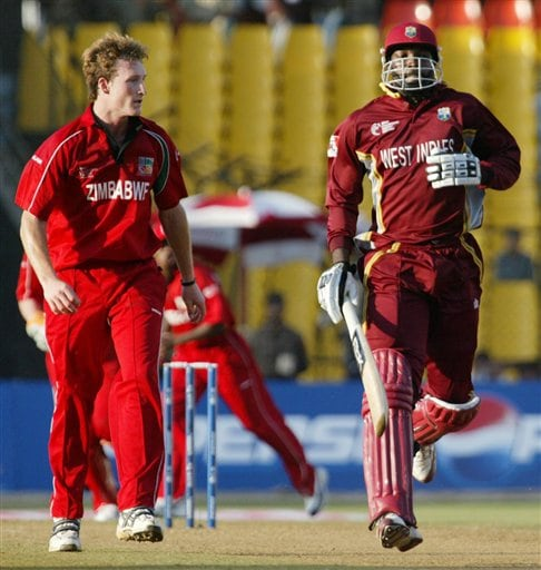 Christopher Gayle, right, of West Indies about to complete a run as Zimbabwe bowler Anthony Ireland, left looks on during the 2nd qualifying match in the Champions trophy in Ahmedabad on Sunday.