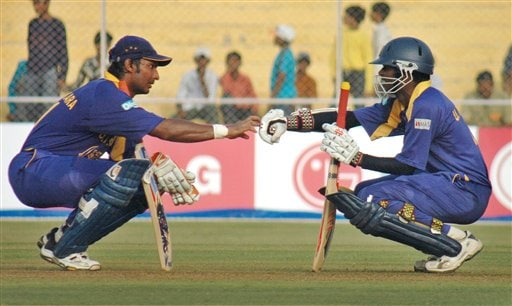 Sri Lankan cricketer Upul Tharanga, right, and Kumar Sangakkara, gesture during a break at the ICC Champions Trophy qualifying match in Ahmedabad on Tuesday.