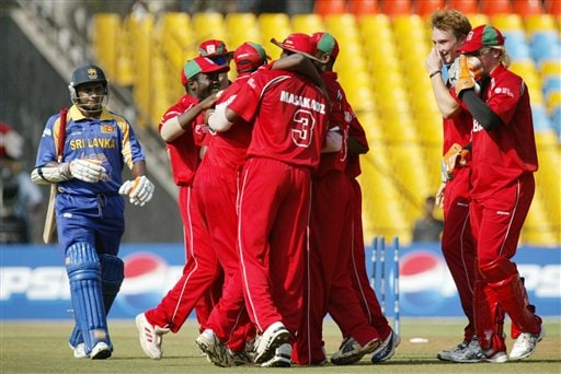 Sri Lankan cricketer Sanath Jayasuriya, left, walks towards the pavilion after being dismissed, as cricketers from Zimbabwe celebrate during the ICC Champions Trophy's qualifying match in Ahmedabad on Tuesday.