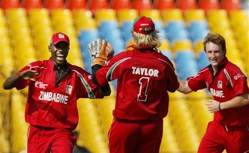 Elton Chigumbura, left, celebrates dismissal of Sanath Jayasuriya of Sri Lanka, unseen, with teammates Brendon Taylor, center, and Anthony Ireland of Zimbabwe during the ICC Champions Trophy's qualifying match in Ahmedabad on Tuesday.