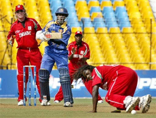 Sri Lankan cricketer Upul Tharanga, second left, looks on as Zimbabwe's Tawanda Mupariwa, on ground, tries to stop a ball during the ICC Champions Trophy's qualifying match in Ahmedabad on Tuesday.