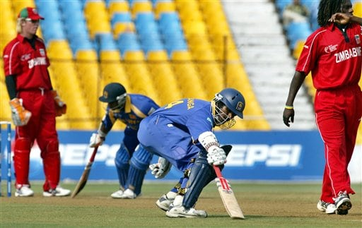 Sri Lankan cricketers Upul Tharanga, second right, and Sanath Jayasuriya, second left, run between the wickets as Zimbabwe's Tawanda Mupariwa, right, and wicket keeper Brendon Taylor, left, look on during the ICC Champions Trophy's qualifying match in Ahmedabad on Tuesday.