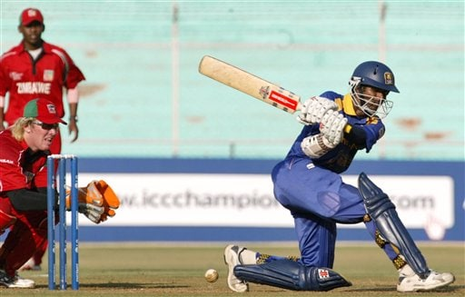 Sri Lankan cricketer Upul Tharanga, right, bats as Zimbabwe wicket keeper Brendon Taylor, left, gestures during the ICC Champions Trophy qualifying match at Ahmedabad on Tuesday.