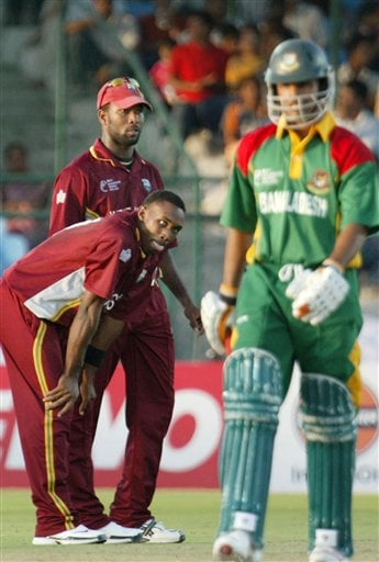 West Indies cricketer Dwayne Bravo, bending, gestures, as teammate Corey Collymore looks on after dismissing Bangladesh's Abdur Razzak, right, during the ICC Champions Trophy qualifying match in Jaipur on Wednesday.