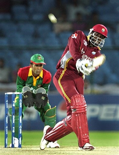 West Indies cricketer Chris Gayle, right, bats as Bangladesh's wicketkeeper Khaled Mashud looks on during the one-day international cricket match for the ICC Champions Trophy, in Jaipur on Wednesday.