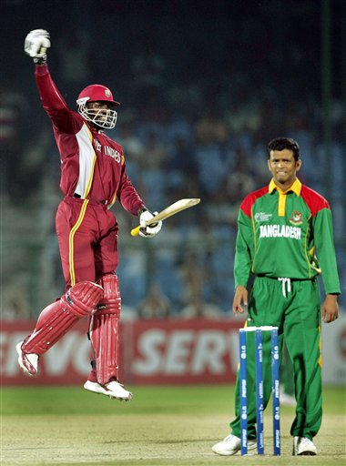 West Indies cricketer Chris Gayle celebrates his century, as Bangladesh's Abdul Razzak looks on during the one-day international cricket match for the ICC Champions Trophy in Jaipur on Wednesday.