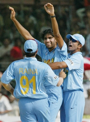 Indian Captain Rahul Dravid, right, congratulates bowler Munaf Patel, center, after taking the wicket of Michel Yardy of England, unseen, during the one-day international cricket match for the ICC Champions Trophy in Jaipur on Sunday.