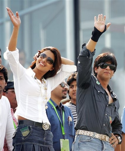 Bollywood actor Shahrukh Khan, right, and actress Priyanka Chopra wave at cricket fans during the one day international cricket match between India and England for the ICC Champions Trophy in Jaipur on Sunday.