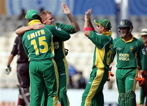South African bowler Shaun Pollock, second left, is hugged by captain Graeme Smith and congratulated by teammates Herschelle Gibbs, second right, and wicketkeeper Mark Boucher after claiming the wicket of New Zealand cricketer Lou Vincent in the one-day international cricket match for the ICC Champions Trophy in Mumbai