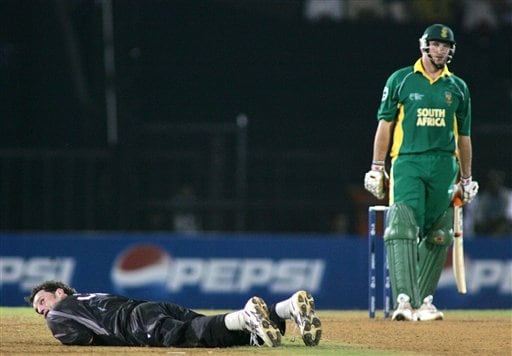 New Zealand's Kyle Mills lies on the ground after a return catch from South African batsman Graeme Smith, right, fell short of his diving hands, in the one-day international cricket match for the ICC Champions Trophy in Mumbai