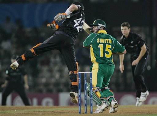 South African batsman Graeme Smith, second right, guides a ball down the off side as New Zealand wicket keeper Brendon McCullum, left, jumps to try and stop it and bowler James Franklin, right, watches, in the one-day international cricket match for the ICC Champions Trophy in Mumbai
