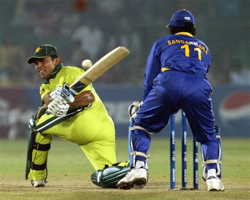 Pakistan's Kamran Akmal plays a shot as Sri Lanka's Kumar Sangakara looks on in the one day international cricket match for the ICC Champions Trophy in Jaipur on Tuesday.