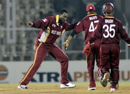 West Indian fielders run towards Chris Gayle, left, after he claimed the wicket of Andrew Symonds of Australia in the one day international cricket match in the ICC Champions Trophy in Mumbai