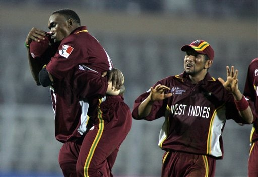 West Indian bowler Dwayne Bravo, center, celebrates along with teammates the dismissal of Australian batsman Michael Clarke in the one day international cricket match in the ICC Champions Trophy in Mumbai