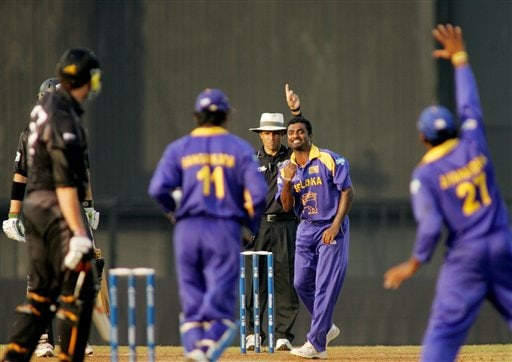 Sri Lanka's Muttiah Muralitharan, center, celebrates the dismissal of New Zealand's Kyle Mills, left, during the Champions trophy cricket match in Mumbai on Friday.
