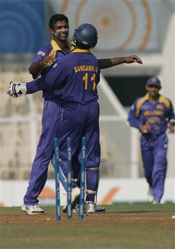 Sri Lanka's Farveez Maharoof, left, is congratulated by teammate Kumar Sangakkara after he bowled out New Zealand's Lou Vincent, unseen, during their Champions trophy cricket match in Mumbai on Friday.