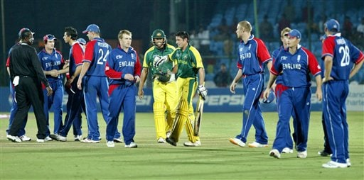 Australia's Michael Hussy, centre right, and Andrew Symonds, walk to the pavilion flanked by England's cricketers after the one-day international cricket match for the ICC Champions Trophy in Jaipur, India, Saturday, October 21, 2006. (AP Photo/Bikas Das)