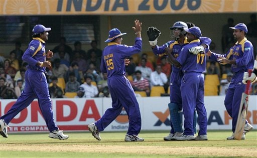 Sri Lankan team members congratulate Kumar Sangakkara, center right with gloves on, after he caught behind South Africa's Boeta Dippenaar, unseen, in their ICC Champions Trophy cricket tournament match in Ahmadabad on Tuesday.