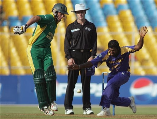Sri Lankan cricketer Muttiah Muralitharan, right, tries to field a ball as South African batsman Abraham Devilliers tries to get out of his way in Ahmadabad on Tuesday.