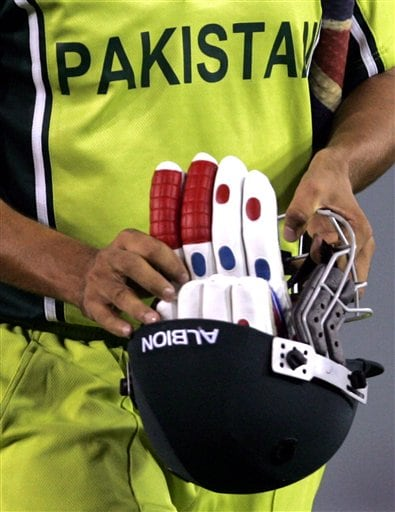 Pakistan's Younis Khan carries back his gloves and helmet after New Zealand's Kyle Mills took his wicket during the one day international cricket match for the ICC Champions Trophy in Mohali