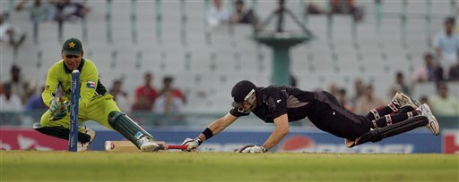 New Zealand's Stephen Fleming, right, dives successfully to complete his run as Pakistan's wicket keeper Kamran Akmal attempts for a run out during the one day international cricket match for the ICC Champions Trophy in Mohali