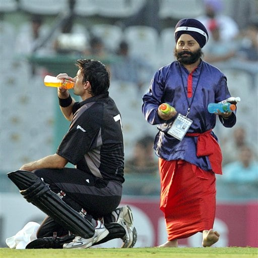 A Sikh carries refreshments as New Zealand's Stephen Fleming, left, drinks during the one day international cricket match against Pakistan for the ICC Champions Trophy in Mohali