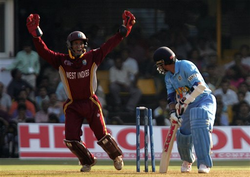 West India's Carlton Baugh jumps up as Indian batsman Sachin Tendulkar is bowled by Ian Bradshaw, unseen, during their ICC Champions Trophy cricket tournament match in Ahmedabad on Thursday.
