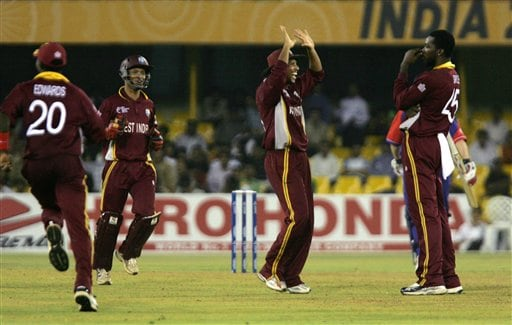 West Indies' Ramnaresh Sarwan, center, congratulates bowler Chris Gayle, right, after Gayle took the wicket of England's Paul Collingwood, unseen, during the ICC Champions Trophy cricket tournament match in Ahmedabad on Saturday.