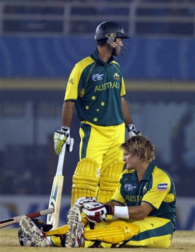 Australia's Shane Watson sits on the pitch after getting leg cramps as captain Ricky Ponting looks for help from the dressing room during the one day international cricket match for the ICC Champions Trophy in Mohali on Sunday.