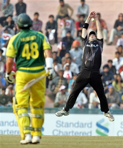 New Zealand's Daniel Vettori, right attempts to take a catch for the dismissal of Australia's Michael Hussey during the one day international semi final cricket match for the ICC Champions Trophy in Mohali