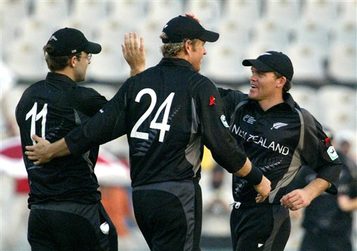New Zealand's Jacob Oram (24) and Lou Vincent, right, congratulate teammate Daniel Vettori, left, for taking the catch of Australian captain Ricky Ponting, unseen, during the one day international cricket semi- final match for the ICC Champions Trophy in Mohali