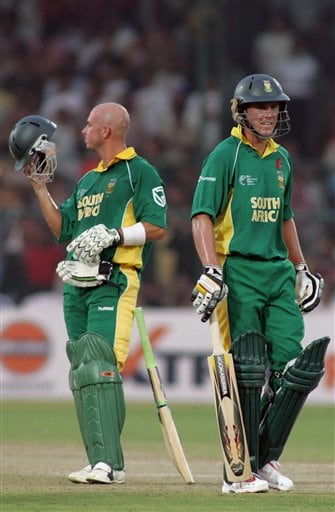South African Herschelle Gibbs, left, and AB de Villiers await a successful run out decision for de Villiers from the third umpire, during the ICC Champions Trophy cricket tournament match against West Indies in Jaipur