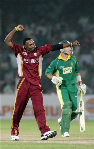 West Indies' Dwayne Bravo, left, celebrates after dismissing South African Herschelle Gibbs, right, during the ICC Champions Trophy cricket tournament semi-final against in Jaipur