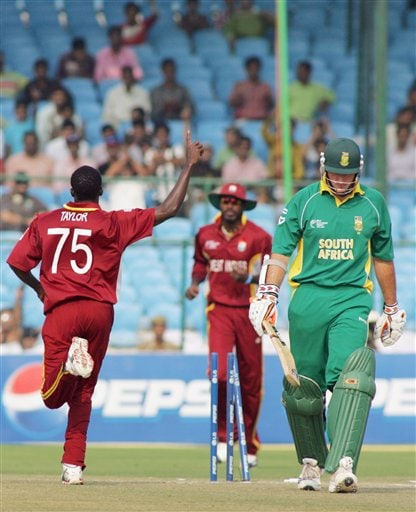 South African cricket captain Graeme Smith, right, walks after he is bowled by West Indies' Jerome Taylor, left, as Christophor Gayle looks on during the ICC Champions Trophy cricket tournament match in Jaipur