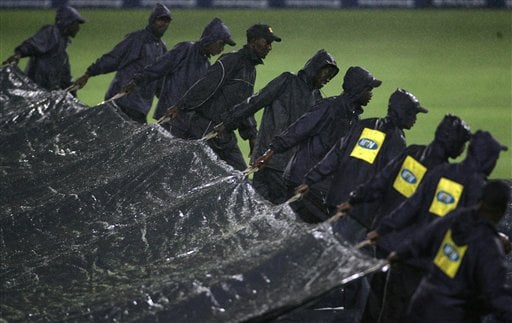 Cricket ground workers pull over the rain cover as the rain delays the start of the 1st match one-day series against South Africa's in Johannesburg, South Africa, Sunday, Nov. 19, 2006. The first one-day international match between South Africa and India was officially called off, because of persistent rain.