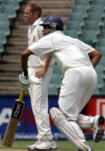 South Africa's bowler Shaun Pollock, left, reacts to runs being made off his bowling by India's batsman VVS Laxman, right, during the third day of the 1st cricket test match against India's second innings at the Wanderers stadium in Johannesburg, South Africa.