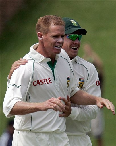 South Africa's bowler Shaun Pollock, left, celebrates with teammate A.B. de Villiers, right, after dismissing India's batsman Mahendra Singh Dhoni, unseen, for 18 runs during the third day of the 1st cricket test match against India's second innings at the Wanderers stadium in Johannesburg, South Africa.