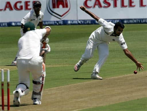 India's bowler Zaheer Khan, right, fields off his own bowling as teammate captain Rahul Dravid, top left, and South Africa's batsman Graeme Smith, bottom left, looks on during the first day of the 2nd Cricket Test match against South Africa at Kingsmead stadium in Durban.