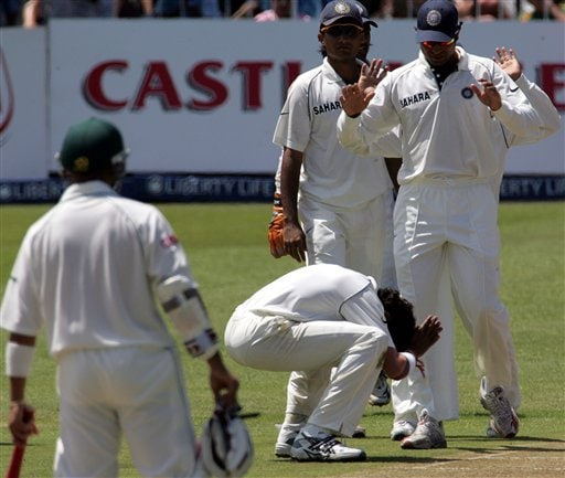India's bowler Shanthakumaran Sreesanth, center, bows down whilst celebrates with teammates the dismiss South Africa's batsman Herschelle Gibbs, unseen, for 63 runs as teammate batsman Ashwell Prince, left, watches on the first day of the 2nd Cricket Test match against South Africa at Kingsmead stadium in Durban.