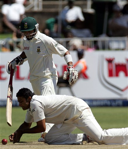 India's bowler Anil Kumble, front, fields off his own bowling as South Africa's batsman Ashwell Prince, back, looks on during the second day of the 2nd Cricket Test match against South Africa at Kingsmead stadium in Durban, South Africa, Wednesday.